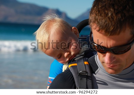 Father and asleep baby son resting on beach after hiking with backpack in beautiful scenery