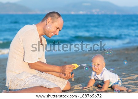 Father and baby are making bubbles - stock photo