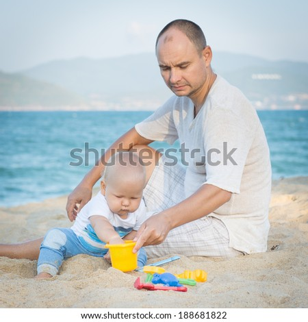 Father and baby are playing beach toys - stock photo