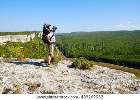 Father and baby boy in backpack travel on beautiful mountains landscape. Active traveler man hiking with child in carrier in nature park. Family tourism, parent with little kid outdoors.