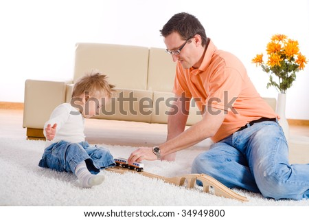 Father and baby boy playing together at home, sitting on floor. - stock photo