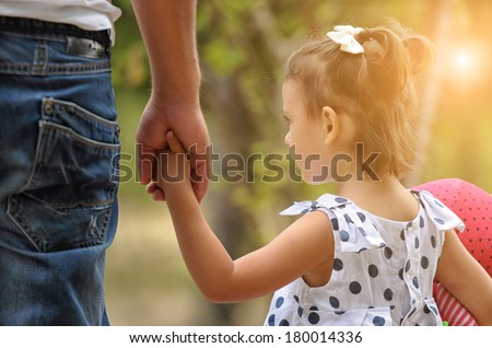 Father and baby girl holding hand in hand  - stock photo