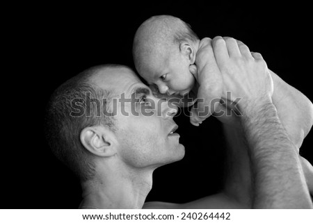 father and baby in front of black background - stock photo
