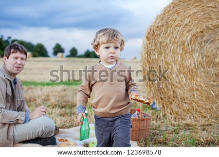 Father and beautiful blond toddler boy making evening picnic on golden straw field