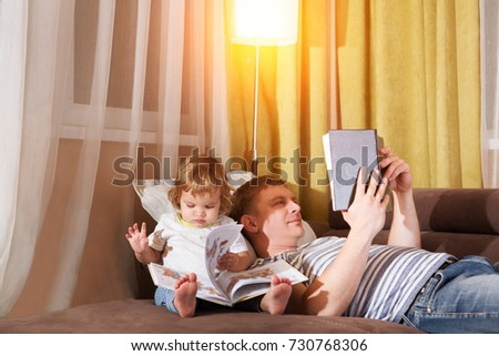 Father and  child are reading books at home. Family Relaxing Indoors.