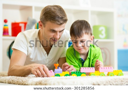 Father and child boy playing construction game together at home. - stock photo