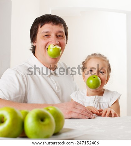 Father and child eating apples. Family at home in the kitchen - stock photo