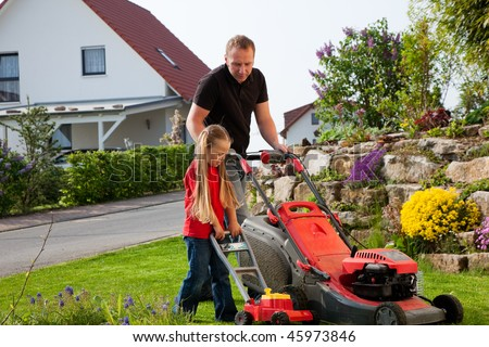 Father and Child mowing the lawn together, daddy has a real lawnmower, the daughter a toy version and is a bit jealous - stock photo