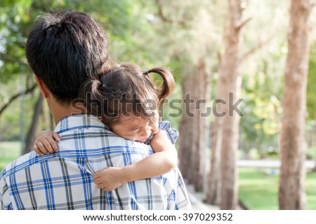 Father and child,sad little girl resting on her father's shoulder in the park - stock photo