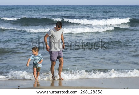 Father and child son walking on a beach in shallow sea water. - stock photo