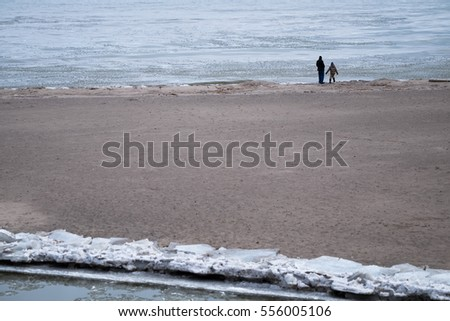 father and child walking on the beach in a cloudy day
