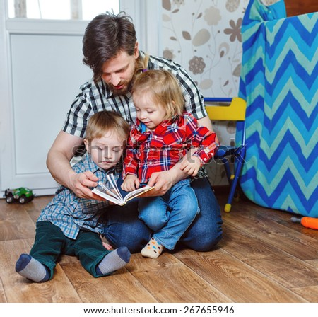 Father and children, brother and sister, reading a book sitting on the floor in the nursery. The concept of child domestic preschool education. - stock photo