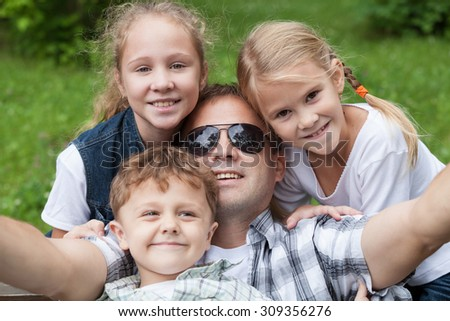 Father and children playing at the park at the day time. - stock photo