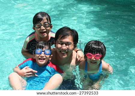 Father and children playing happily in the pool - stock photo