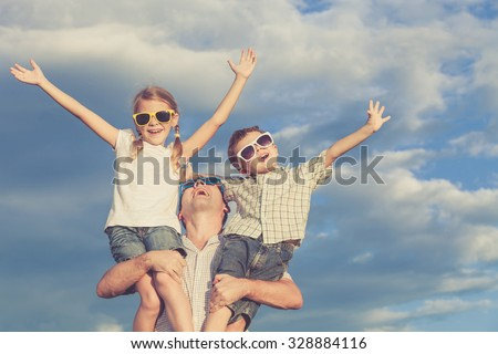 Father and children playing in the park  at the day time. Concept of friendly family. Picture made on the background of blue sky. - stock photo