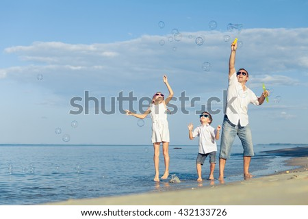 Father and children  playing on the beach at the day time. Concept of friendly family.