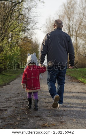 Father and daughter are holding hands.