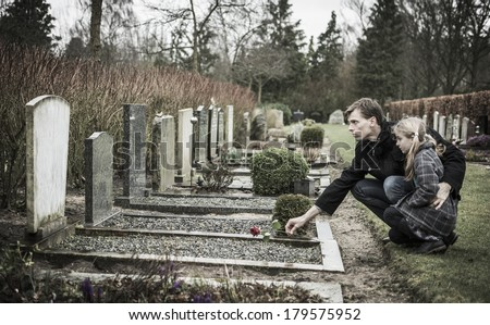 Father and daughter at grave of deceased mother. Widower - stock photo