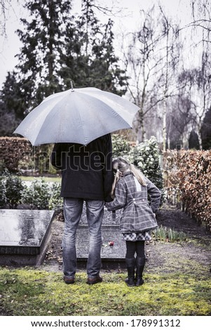 Father and daughter at mummy's gravestone - stock photo