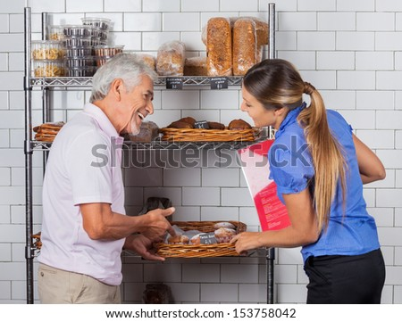 Father and daughter buying muffins at supermarket - stock photo