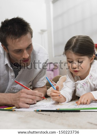 Father and daughter coloring book together on floor at home - stock photo