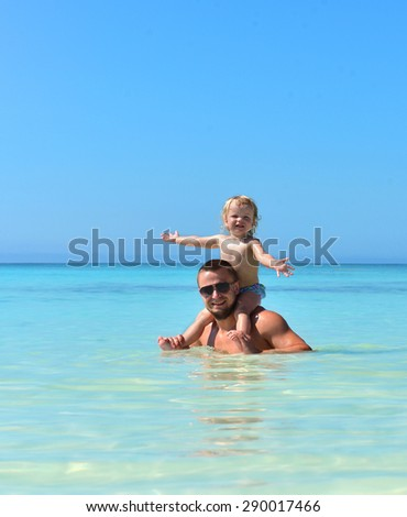 Father and daughter. Dad holding two year old baby girl on neck happy playing smiling in water on sea beach tropical vacation holidays - stock photo
