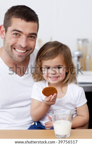 Father and daughter eating biscuits with milk in the kitchen - stock photo