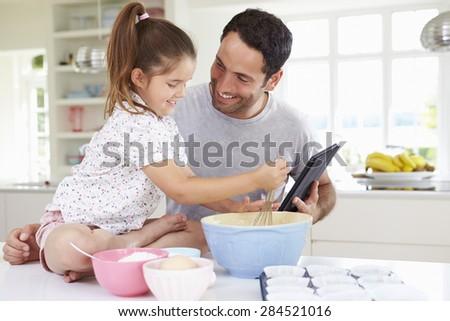 Father And Daughter Following Cake Recipe On Digital tablet - stock photo