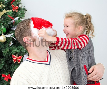 Father and daughter having fun at the christmas. Girl trying to put on Santa's hat on father. - stock photo