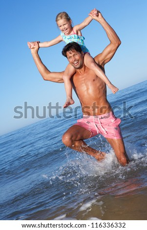 Father And Daughter Having Fun On Beach - stock photo