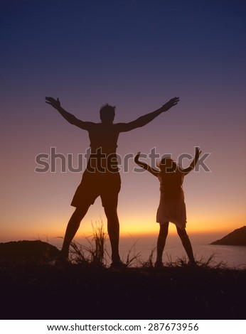 Father and daughter having fun on sunset background over the sea bay