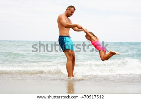 Father and daughter having fun on the beach.