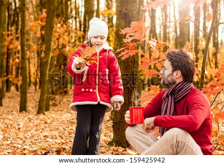 Father and daughter having fun outdoor in the park during an autumn picnic -  happy loving active caucasian family in nature - stock photo