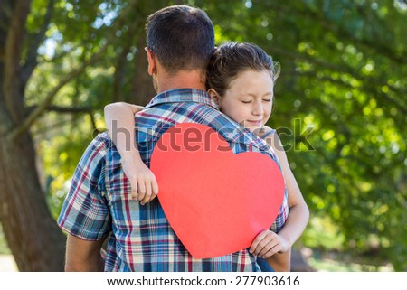 Father and daughter hugging in the park on a sunny day - stock photo