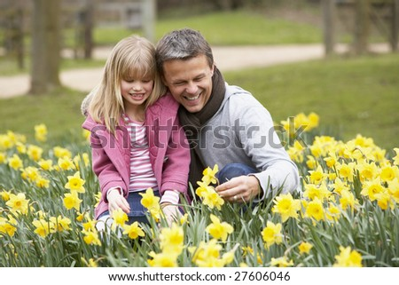 Father And Daughter In Daffodils - stock photo