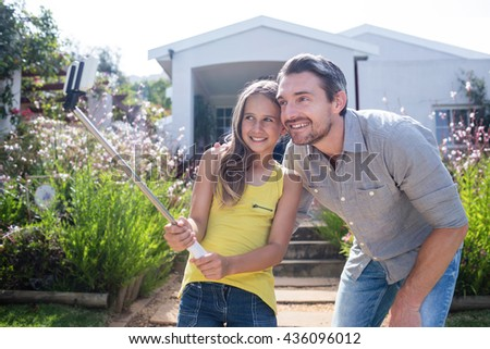 Father and daughter in garden taking a selfie with selfie stick - stock photo