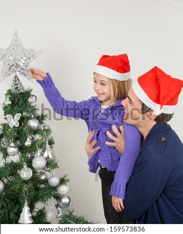 Father and daughter in Santa hats looking at Christmas tree at home - stock photo