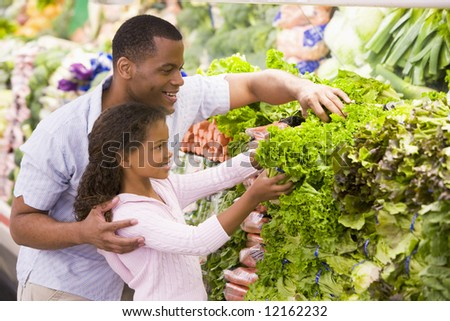 Father and daughter in supermarket produce section - stock photo