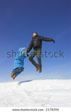 Father and daughter jumping in the blue sky - stock photo