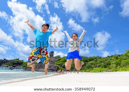 Father and daughter jumping with happy on beach near the sea under blue sky and cloud of summer at Koh Similan Island in Mu Ko Similan National Park, Phang Nga province, Thailand - stock photo