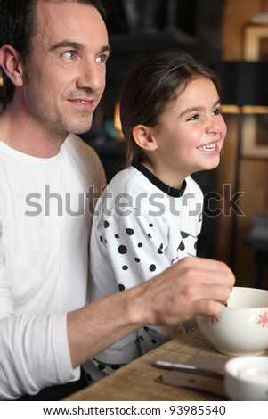 Father and daughter laughing at breakfast - stock photo
