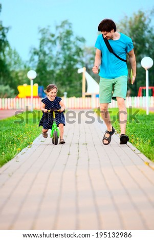 Father and daughter learning to ride a bicycle  - stock photo