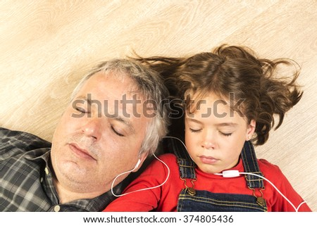 Father and daughter listening to music together with headphones stretched on a wooden floor at home - stock photo