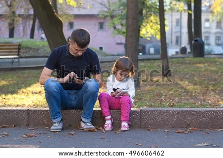 Father and daughter looking at the mobile phone while sitting outdoor in an park - enjoying modern technology.