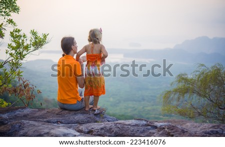 Father and daughter  near cliff on the top of tropical island mountain on sunset - stock photo