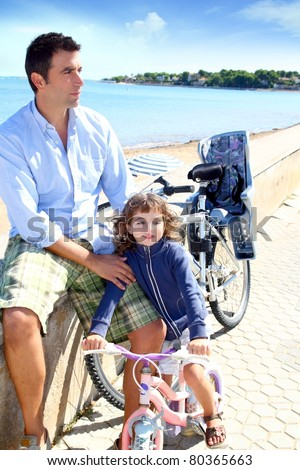 father and daughter on bicycle in beach during summer vacation - stock photo