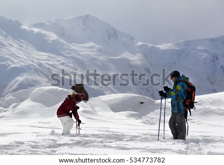 Father and daughter on ski resort after snowfall in winter day. Caucasus Mountains. Georgia, region Gudauri.
