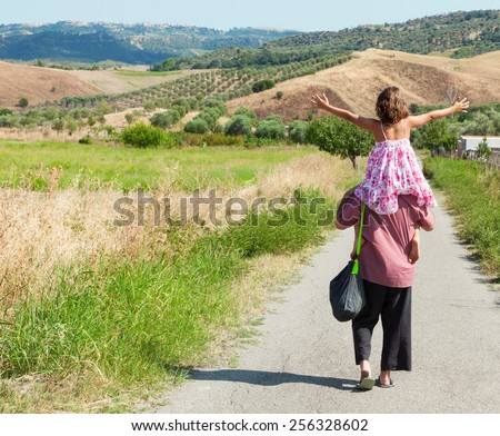father and daughter on the road, rear view - stock photo