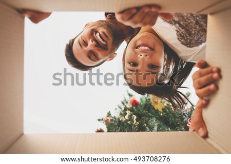 Father and daughter opening a Christmas present, view from inside of the box