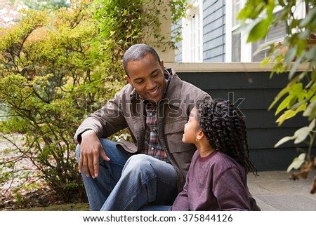 Father and daughter outside house - stock photo